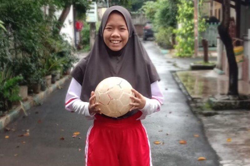 Foto remaja perempuan membawa bola sepak di sebuah gang pemukiman
